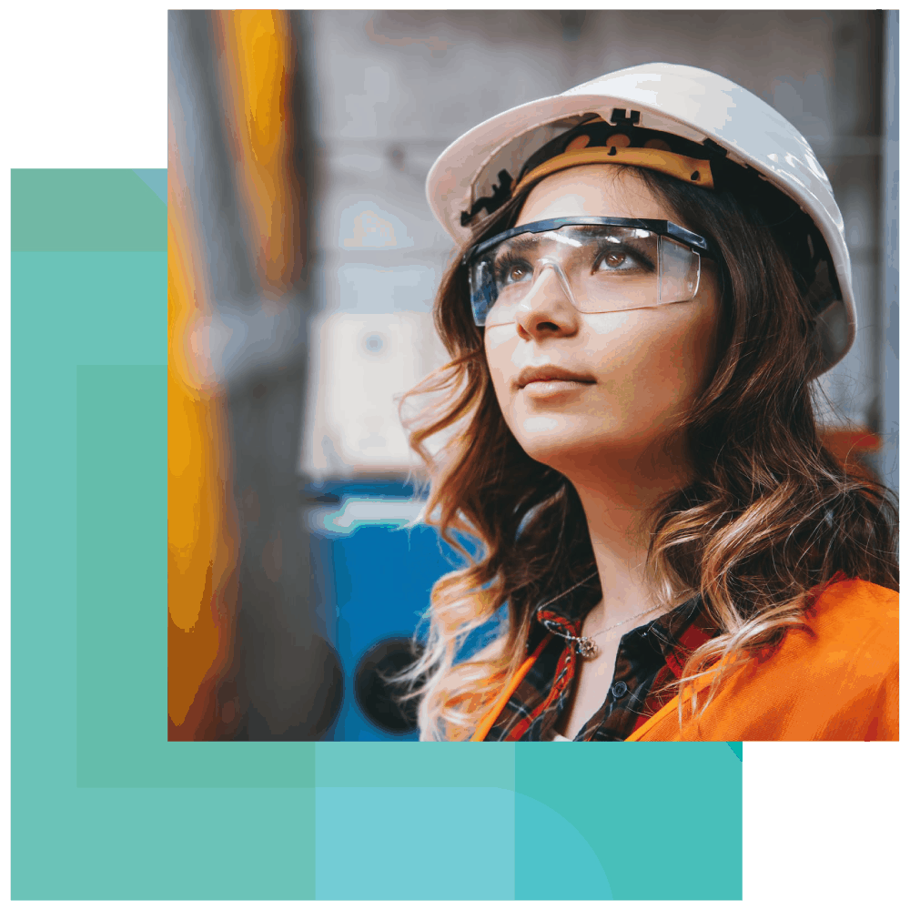 An employee wearing a hard hat, safety glasses, and safety vest worries about her student loans while at work