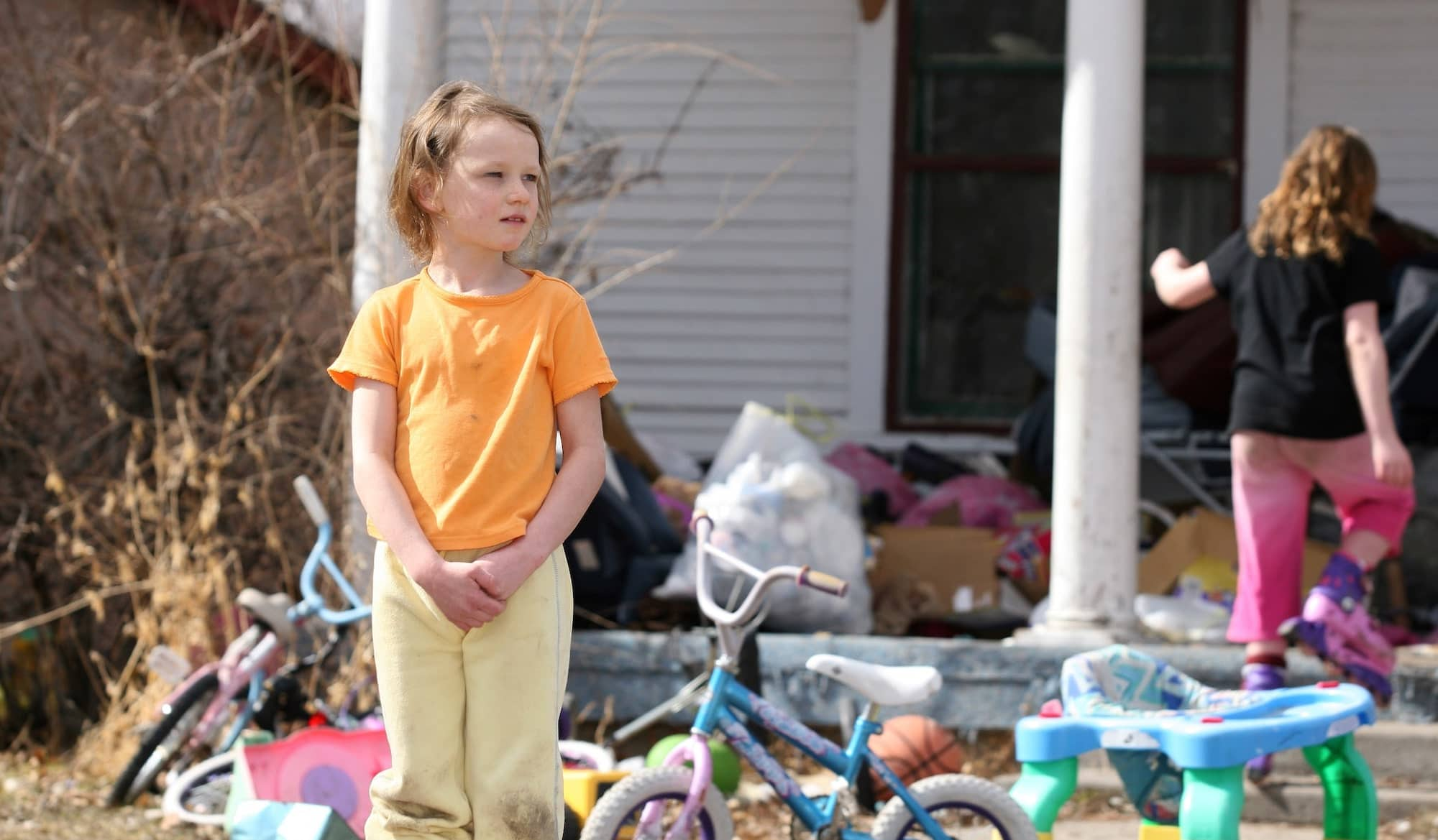 A child in poverty stands in front of a foreclosed home as her sister walks through their belongings outside.
