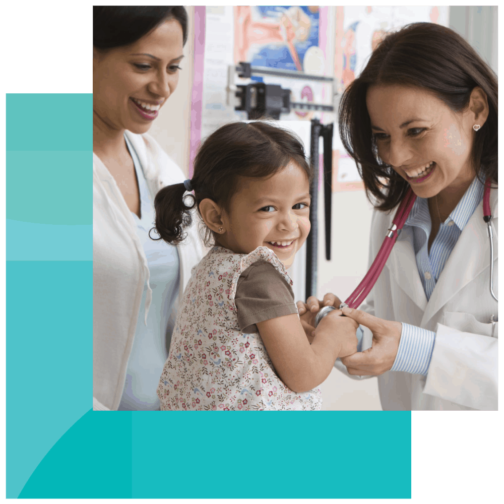 Everyone smiles as a pediatrician lets a young girl play with her stethoscope