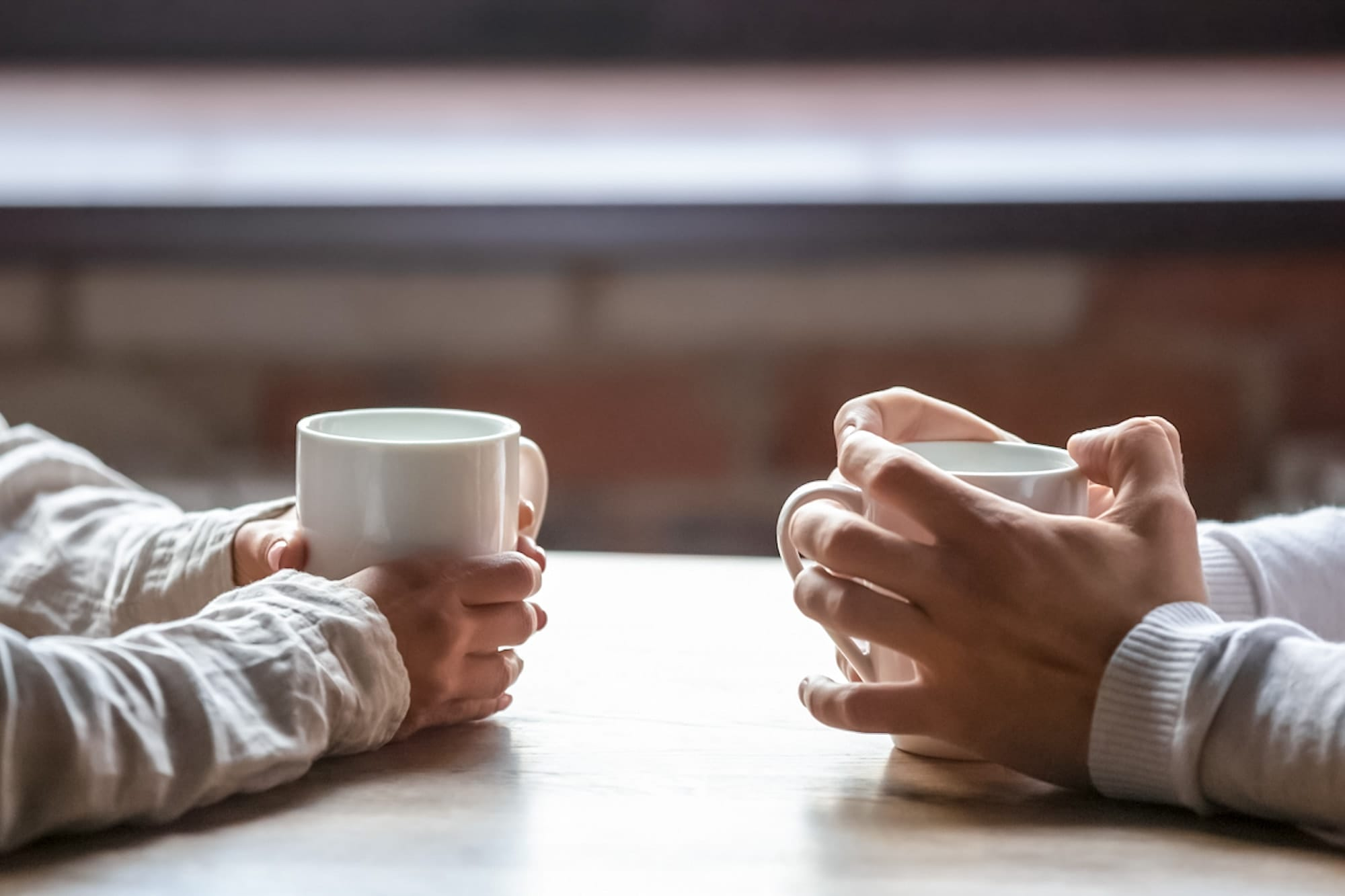 A credit union employee and member having a conversation over a cup of coffee