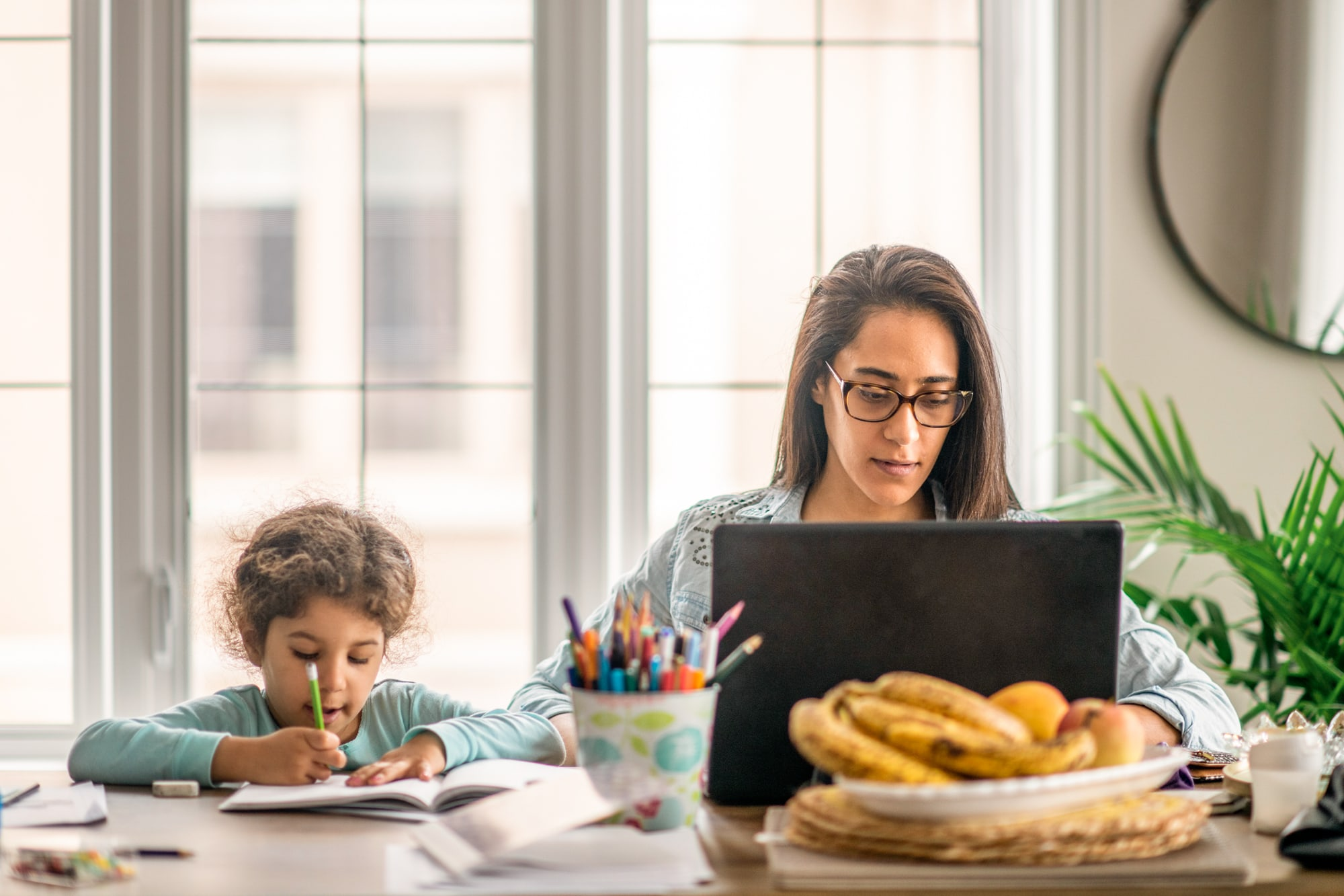 A mother tries to work from home with her child doing homework beside her