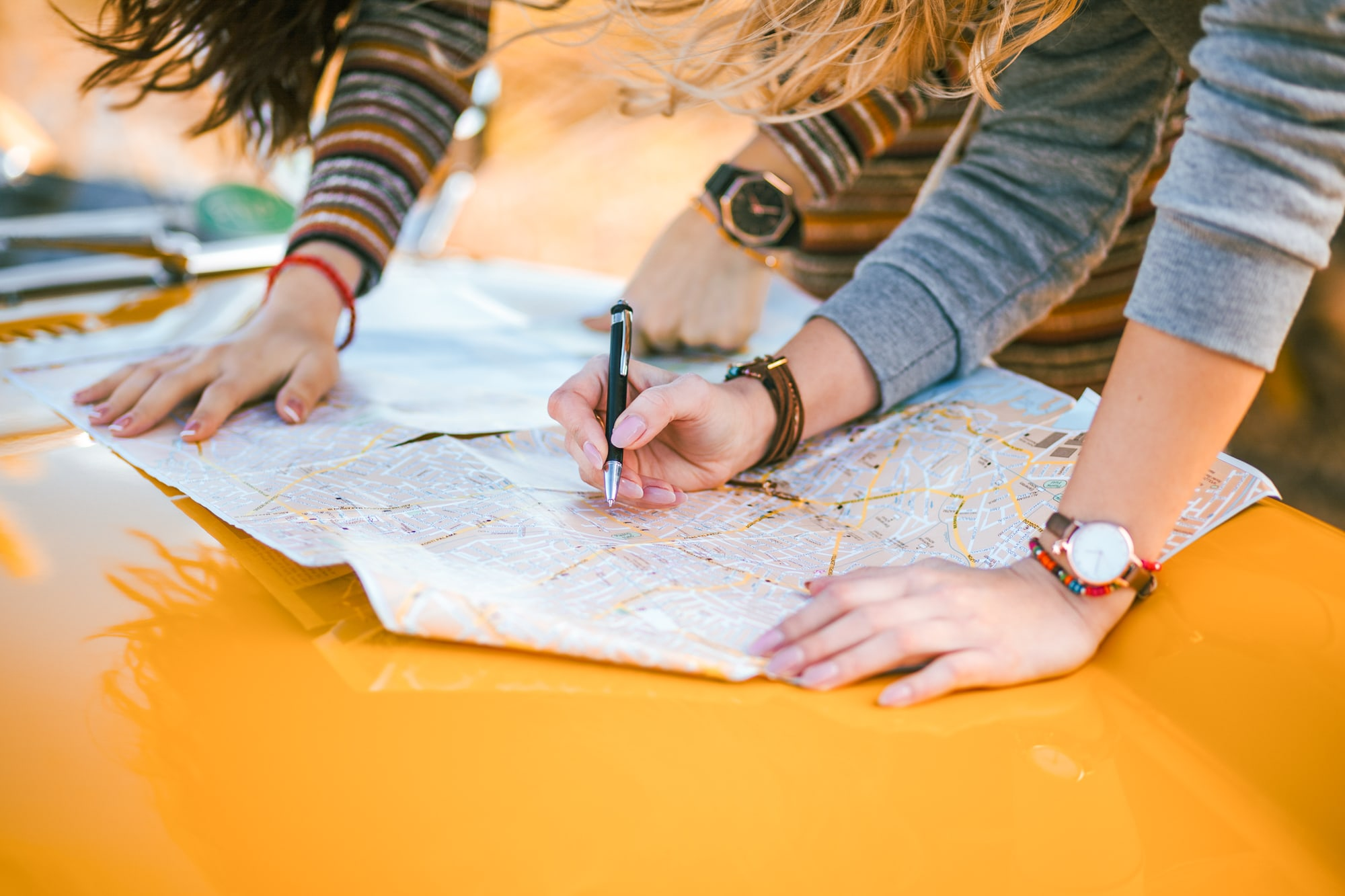 Two women use a map to plan their roadtrip